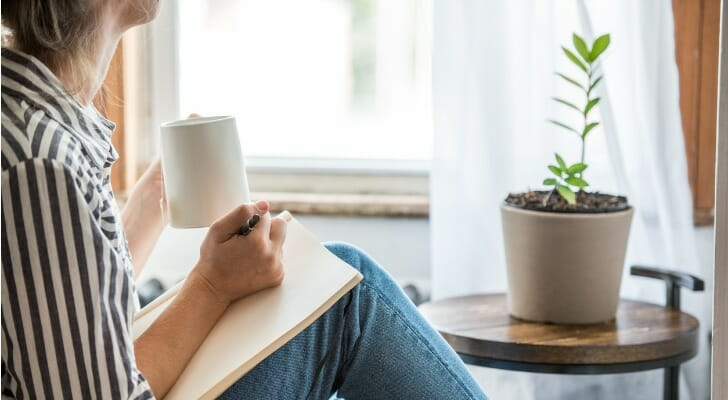 Image shows a person taking a break from work; they are sitting by a window and a potted plant, with a mug in one hand and a notebook and pen in the other. SmartAsset analyzed data to find the best cities for work-life balance.